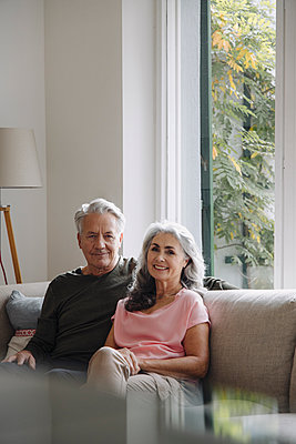 Portrait of senior couple relaxing on couch at home - p300m2156260 by Gustafsson