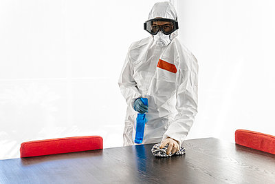 Woman wearing protective clothes, sanitizing her home, wiping table - p300m2170737 by Javier De La Torre Sebastian
