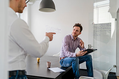 Male entrepreneur planning with colleague during meeting in office - p300m2265200 by Daniel Ingold