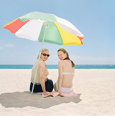 Rear view of a mature woman sitting with her daughter on the beach - p3741547 by Karin Smeds