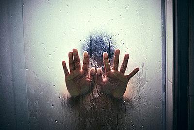 Hands of Hispanic boy leaning on shower door - p555m1304118 by Paco Navarro