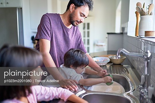 Father and kids doing dishes at kitchen sink - p1023m2201080 by Trevor Adeline