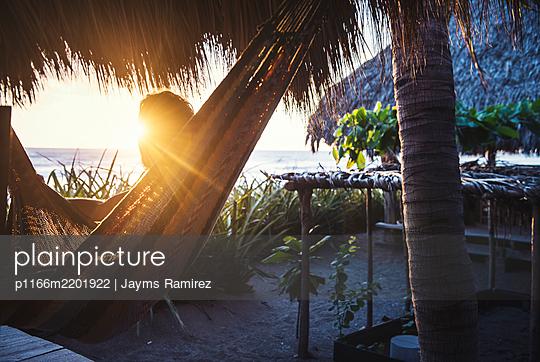 guy enjoying nicaraguan sunset in hammock - p1166m2201922 by Jayms Ramirez