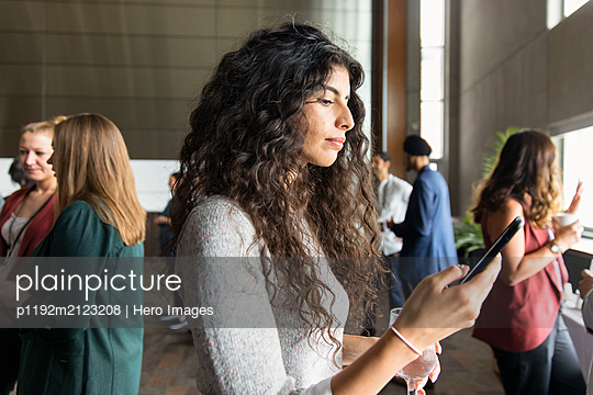 Businesswoman using smart phone at conference - p1192m2123208 by Hero Images