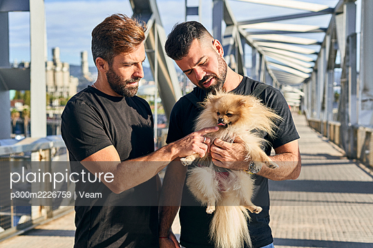 Homosexual couple with dog spending on footbridge during sunny day - p300m2226759 by Veam