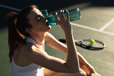 Woman drinking water during a tennis game - p1315m2131517 by Wavebreak