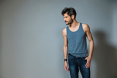 Man wearing jeans and muscle shirt - p1355m1208904 by Tomasrodriguez