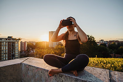 Sporty woman using VR glasses while sitting on retaining wall in city during sunset - p300m2202928 by Eugenio Marongiu
