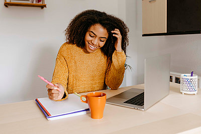 Smiling woman working over document while sitting with laptop at home office - p300m2257290 by Tania Cervián