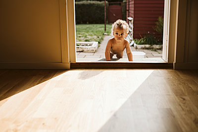 Toddler crawling through door - p312m2162180 by Stina Gränfors
