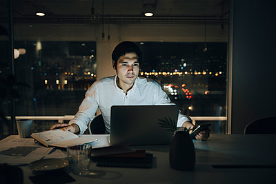 Determined businessman illuminated by laptop while working late in dark office - p426m2194746 by Maskot