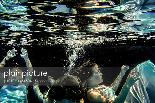 Children floating underwater - p1019m1461894 by Stephen Carroll