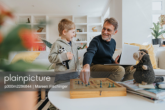 Father in home office and son playing a board game at home, Viersen, NRW, Germany - p300m2286844 von Mareen Fischinger