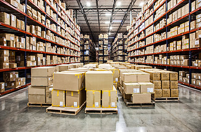 View down aisles of racks holding cardboard boxes of product on pallets  in a large distribution warehouse - p1100m1575482 by Mint Images