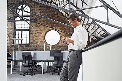 Mature businessman using smartphone in modern office - p300m1562708 by Philipp Dimitri