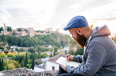 Man at observation point drawing a sketch of the Alhambra, Granada, Spain - p300m2188219 by Daniel González
