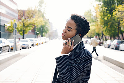 Young businesswoman with eyes closed on phone call in city - p300m2241811 by Katharina und Ekaterina