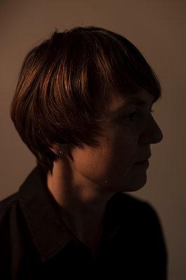 Porträt einer brünetten Frau im Zwielicht - p552m1538695 von Leander Hopf