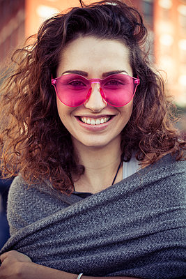 Woman wearing pink sunglasses, smiling cheerfully, portrait - p623m1221422 by Gabriel Sanchez