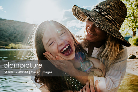 Mom holding young happy daughter while daughter laughs - p1166m2208014 by Cavan Images