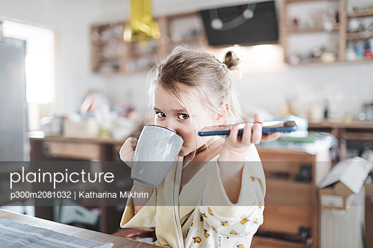 Portrait of little girl with smartphone drinking tea in the kitchen - p300m2081032 by Katharina Mikhrin