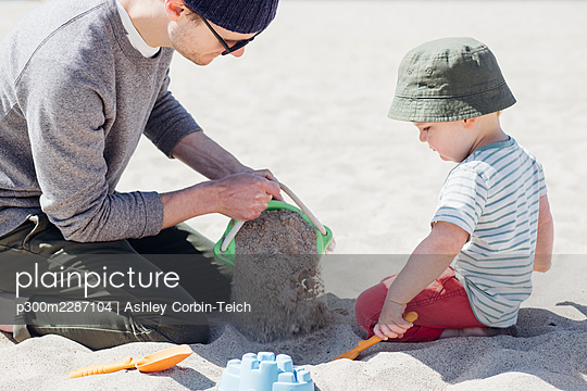Man and son playing with sand together at beach during sunny day - p300m2287104 by Ashley Corbin-Teich