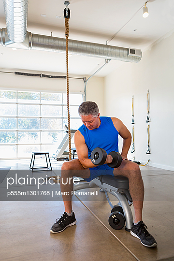 Mixed Race man curling dumbbell in gymnasium - p555m1301768 by Marc Romanelli