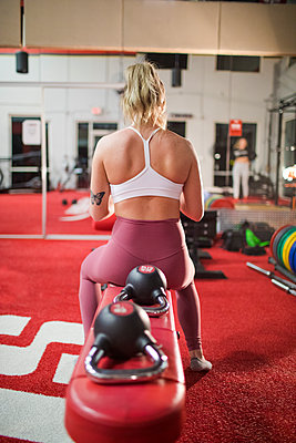 Rear view of woman sitting on bench at the gym during a workout - p1166m2084288 by Cavan Images