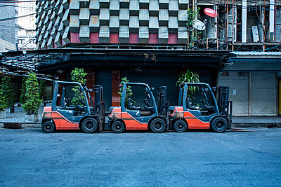 fork lift trucks parked on empty street in the Patpong area of Bangkok - p1166m2174231 by Cavan Images