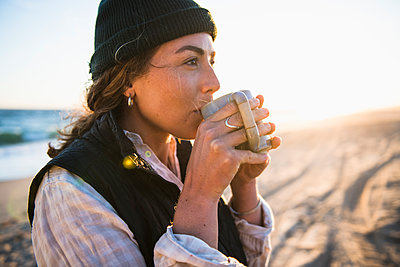 Young woman enjoying drink in mug while beach car camping alone - p1166m2285578 by Cavan Images