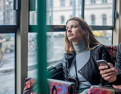 Contemplating young businesswoman sitting by male colleague's hand holding smart phone in bus - p300m2240031 by LOUIS CHRISTIAN