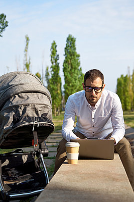 Mid adult male entrepreneur sitting with laptop on retaining wall by baby stroller - p300m2282852 by Veam
