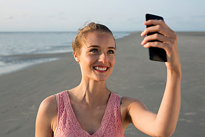 Young woman on beach takes a selfie - p341m1480705 by Mikesch