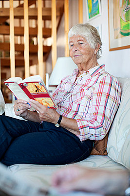 Elderly woman reading novel while sitting on sofa in living room - p4269317f by Maskot