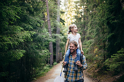 Smiling father carrying daughter on shoulder while walking in forest - p426m2212187 by Maskot