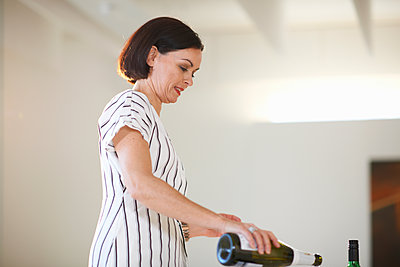 Mature woman pouring white wine at art gallery opening - p429m1408039 by Peter Muller