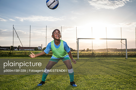 Young football player heading the ball on football ground - p300m1581339 von Fotoagentur WESTEND61
