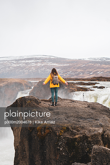 Iceland, woman standing at Godafoss waterfall - p300m2004678 von Kike Arnaiz