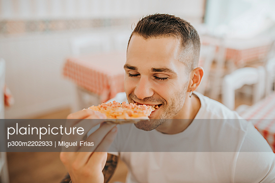 Close-up of young man with eyes closed eating pizza while sitting in restaurant - p300m2202933 by Miguel Frias