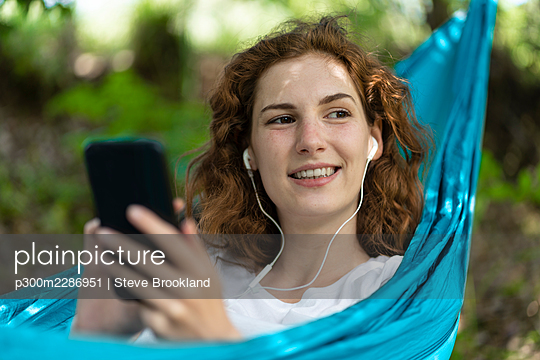 Woman relaxing in hammock and listening to music on her smartphone with headphones in Portugal - p300m2286951 von Steve Brookland