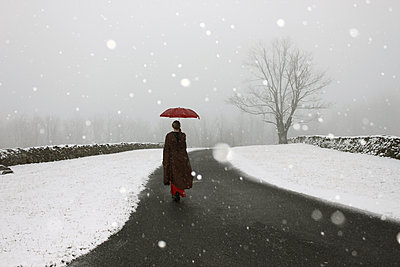 Woman with umbrella in snow - p1019m2141660 by Stephen Carroll