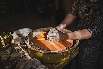 Midsection of craftsperson molding clay on pottery wheel at dark workshop - p1166m1512993 by Cavan Images