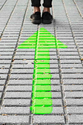 Man standing in front of a green arrow painted on the sidewalk - p1423m2185602 von JUAN MOYANO