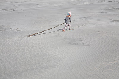Toddler boy carries piece of wood over the beach - p1612m2223687 by Heidi Coppock-Beard