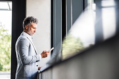 Mature businessman holding cell phone at the window - p300m1536335 by HalfPoint