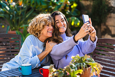 Happy daughter taking selfie with mother through mobile phone at front yard - p300m2276059 by Manu Padilla Photo