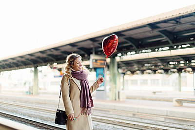 Woman with heart shaped balloon at train station, Firenze, Toscana, Italy - p429m2202358 by Sofie Delauw