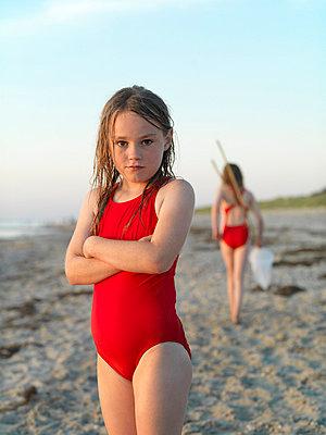 Girl standing on sandy beach - p429m746921f by Soren Nielsen