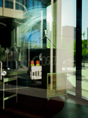 A closed sign hanging in a shop window - p801m2257702 by Robert Pola