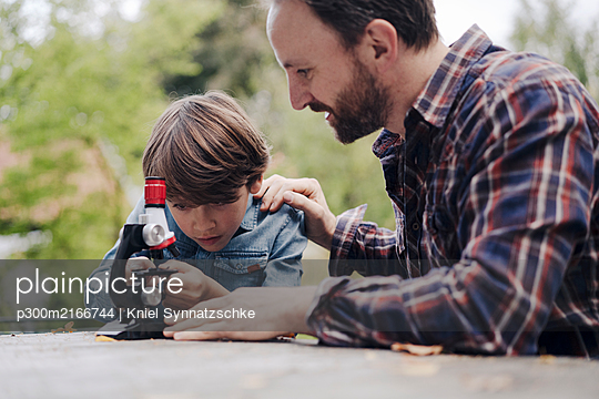 Father and son looking at objects under a microscope - p300m2166744 von Kniel Synnatzschke